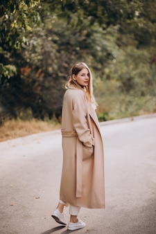 Młoda kobieta w beżowym płaszczu spaceru w parku