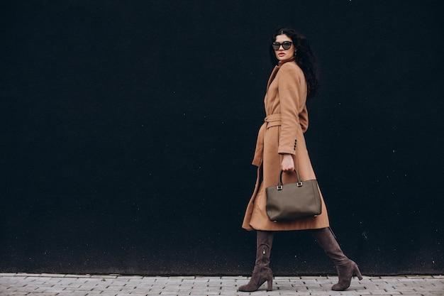 Młoda kobieta w beżowym płaszczu spacerująca na zewnątrz na tle czarnej ściany