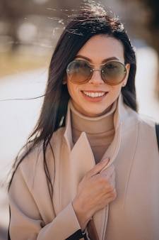 Młoda kobieta w beżowym płaszczu spacerująca po ulicy