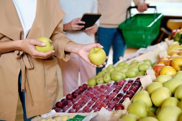 Młoda kobieta w beżowym płaszczu trzyma dwa dojrzałe jabłka granny smith