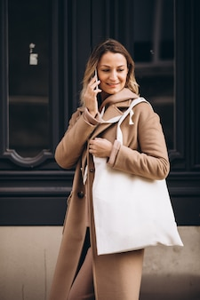 Młoda kobieta w beżowym płaszczu za pomocą telefonu poza ulicą