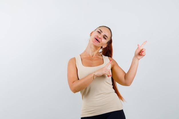 Młoda kobieta w beżowym podkoszulku bez rękawów, wskazująca na prawy górny róg i wyglądająca wesoło, widok z przodu.