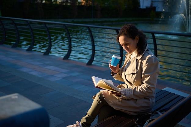 Młoda kobieta w beżowym trenczu siedząca na ławce w parku na tle jeziora, pijąca kawę lub gorący napój w papierowym kubku z recyklingu na wynos i czytająca książkę, ciesząc się odpoczynkiem od cyfrowych gadżetów