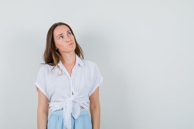 Młoda kobieta w białej bluzce i jasnoniebieskiej spódnicy stoi prosto i myśli o czymś i patrzy zamyślony