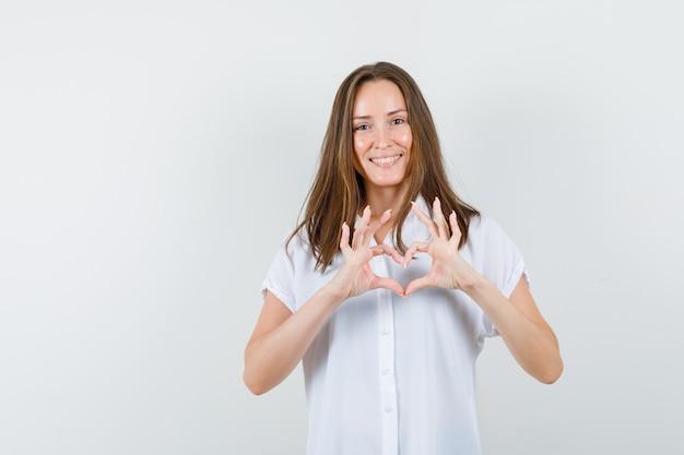 Młoda kobieta w białej bluzce pokazuje gest miłości i szuka ukochanej