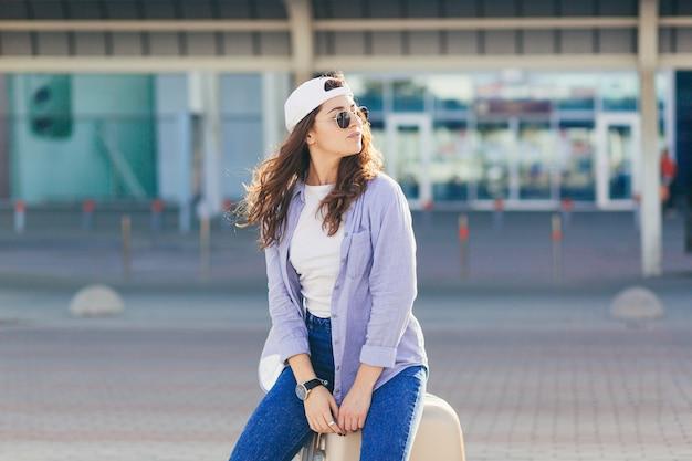 Młoda kobieta w białej czapce z walizką