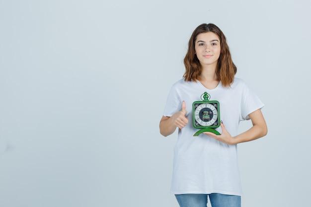 Młoda kobieta w białej koszulce, dżinsy trzymając zegar, pokazując kciuk do góry i patrząc wesoło, widok z przodu.