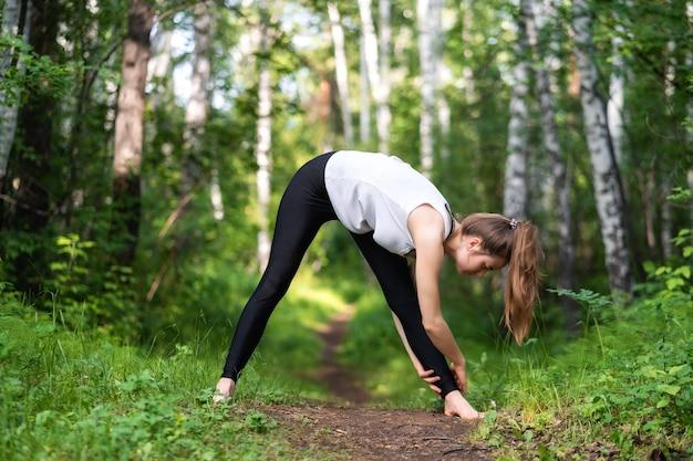 Młoda kobieta w białej koszulce i czarnych legginsach rozciąga się na stojąco, ściskając swoje goleni nogi, stojąc boso w lesie