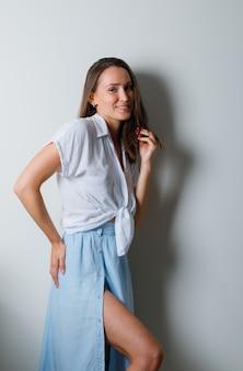 Młoda kobieta w białej koszulce i jasnoniebieskiej spódnicy, trzymając rękę na biodrze, chowając włosy i wyglądając uroczo