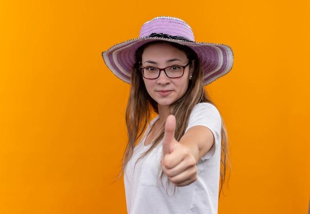 Młoda kobieta w białej koszulce na sobie letni kapelusz, uśmiechając się radośnie pokazując kciuki do góry stojąc na pomarańczowej ścianie