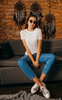 Młoda kobieta w białej koszulce pozowanie studio na tle ściany z cegły