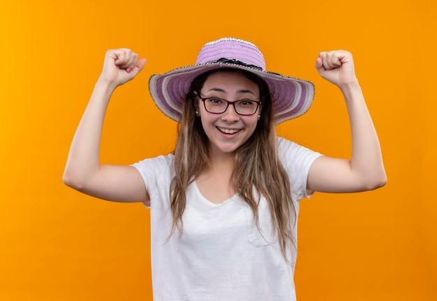 Młoda kobieta w białej koszulce w letnim kapeluszu, podnosząc pięści, szczęśliwa i podekscytowana, ciesząc się swoim sukcesem stojąc nad pomarańczową ścianą