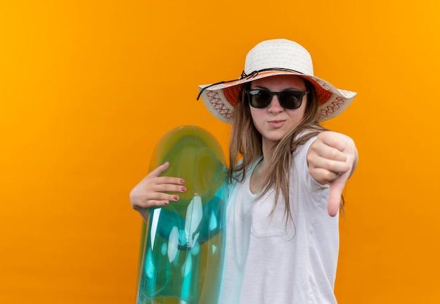 Młoda kobieta w białej koszulce w letnim kapeluszu trzyma nadmuchiwany pierścionek, patrząc niezadowolony, pokazując kciuk w dół stojąc nad pomarańczową ścianą