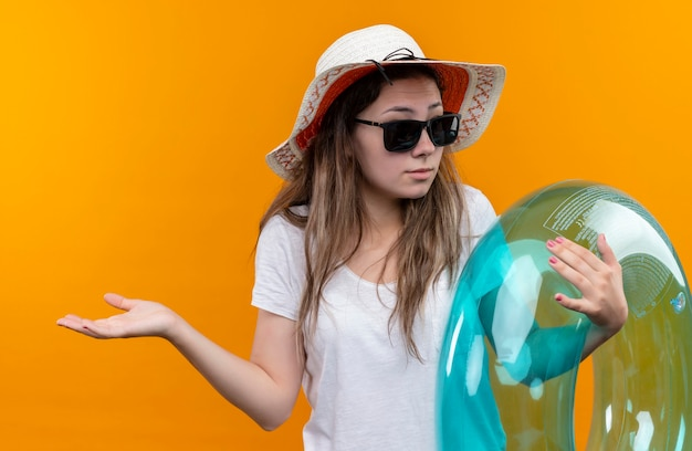Młoda kobieta w białej koszulce w letnim kapeluszu trzymająca nadmuchiwany pierścień wyglądająca na zdezorientowaną i niepewną, rozkładającą dłonie na bok, stojącą nad pomarańczową ścianą