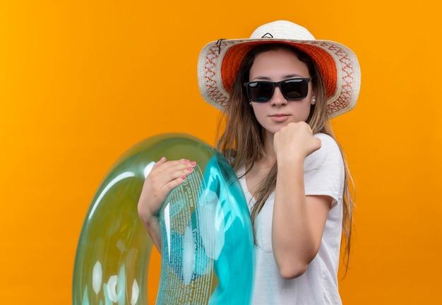 Młoda kobieta w białej koszulce w letnim kapeluszu trzymająca nadmuchiwany pierścień zaciskająca pięść, wyglądająca na pewną siebie z poważnym wyrazem twarzy, stojąca nad pomarańczową ścianą