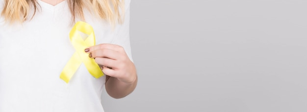 Młoda kobieta w białej koszulce z żółtą wstążką symbol świadomości samobójstwa