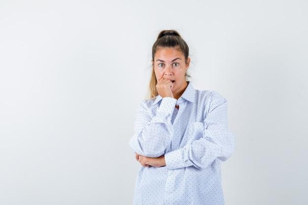 Młoda kobieta w białej koszuli gryzie pięść emocjonalnie i wygląda niespokojnie
