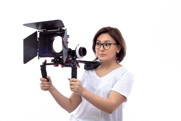 Młoda kobieta w białej koszuli i czarnych szkłach trzyma kamerę telewizyjną