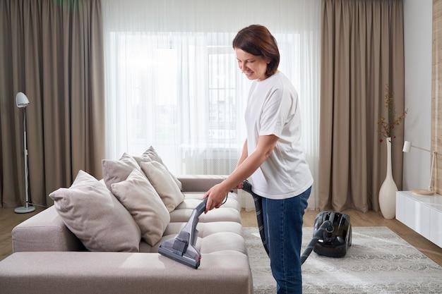 Młoda kobieta w białej koszuli i dżinsach, czyszczenie dywanu pod sofą z odkurzaczem w salonie, kopia przestrzeń. koncepcja prac domowych, sprzątania i obowiązków domowych