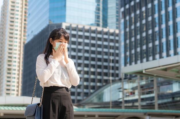 Młoda kobieta w białej koszuli idzie do pracy mdłości z kaszlem
