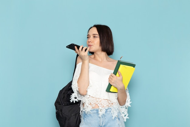 Młoda kobieta w białej koszuli, niebieskie dżinsy i czarną torbę, trzymając zeszyty i telefon na niebiesko