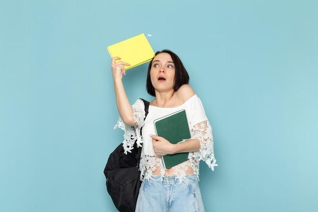 Młoda kobieta w białej koszuli niebieskie dżinsy i czarną torbę trzymając zeszyty na niebiesko