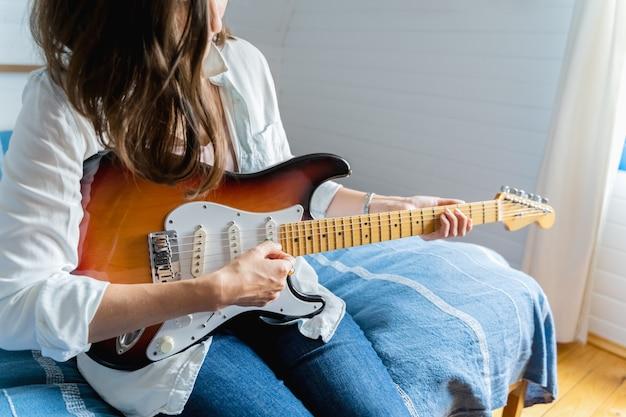 Młoda kobieta w białej koszuli, niebieskie dżinsy siedzi na łóżku i gra na gitarze elektrycznej w domu