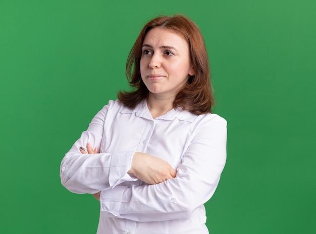 Młoda kobieta w białej koszuli patrząc na bok z poważną twarzą z rękami skrzyżowanymi stojąc na zielonej ścianie