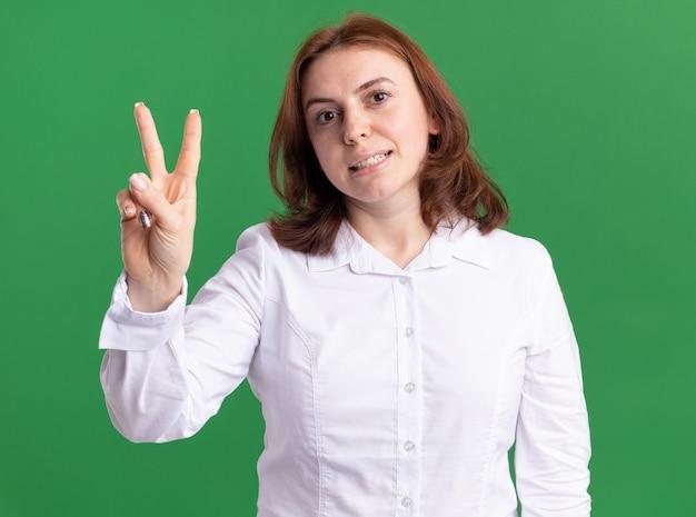 Młoda kobieta w białej koszuli patrząc z przodu pokazuje i wskazuje w górę palcami numer dwa iing na zielonej ścianie