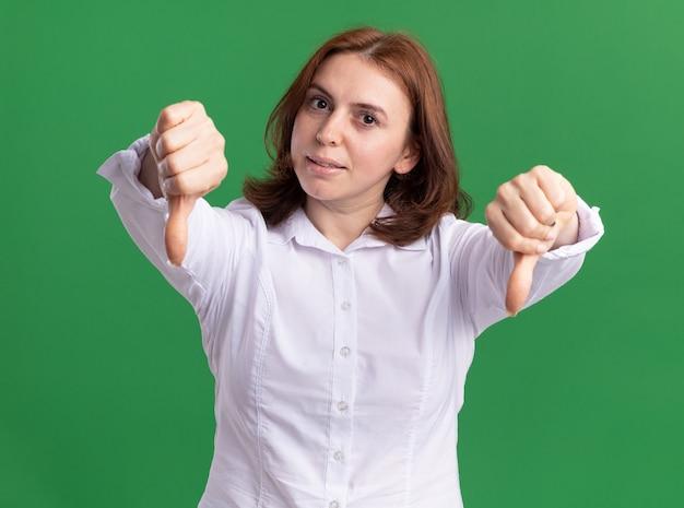 Młoda kobieta w białej koszuli patrząc z przodu z poważną twarzą pokazującą kciuki do góry obiema rękami stojącymi na zielonej ścianie