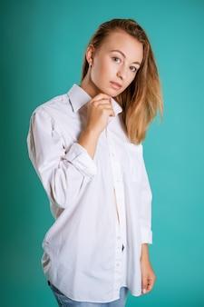 Młoda kobieta w białej koszuli pozowanie