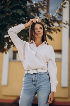 Młoda kobieta w białej koszuli spacerująca poza letnimi ulicami