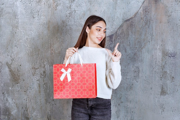 Młoda kobieta w białej koszuli trzyma czerwoną torbę na zakupy i wygląda na zdezorientowaną i zamyśloną