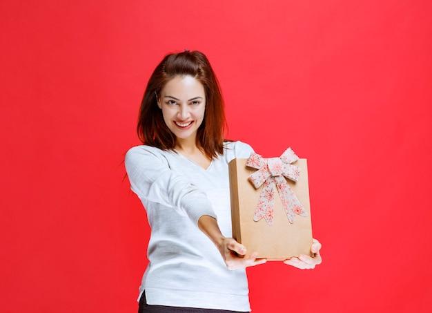 Młoda kobieta w białej koszuli trzyma kartonowe pudełko i prezentuje je komuś