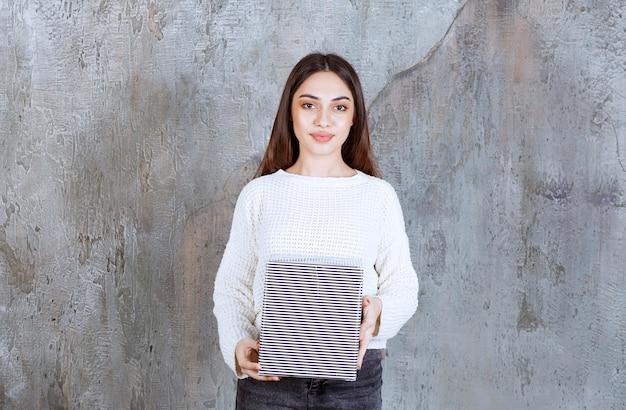 Młoda kobieta w białej koszuli trzyma srebrne pudełko upominkowe