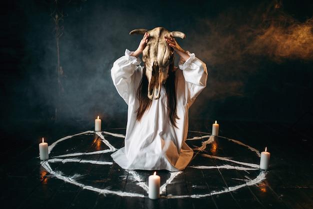 Młoda kobieta w białej koszuli trzyma w rękach czaszkę zwierzęcia, koło pentagramowe ze świecami, dookoła dym. rytuał czarnej magii, okultyzm