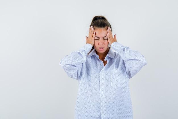 Młoda kobieta w białej koszuli, trzymając się za ręce na skroniach i wyglądając na zmęczonego