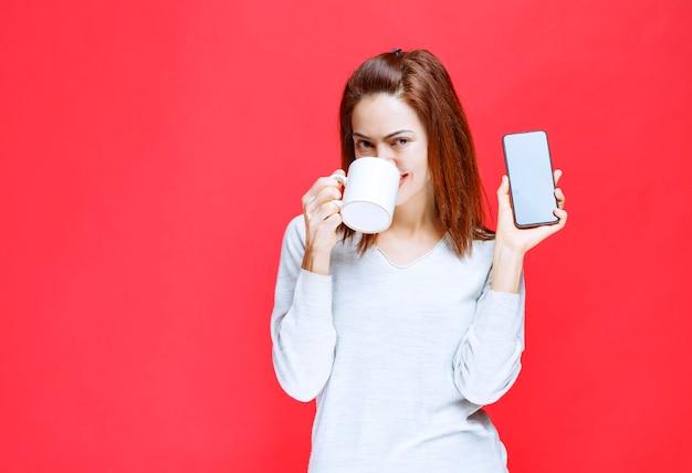 Młoda kobieta w białej koszuli trzymająca biały kubek kawy i czarny smartfon