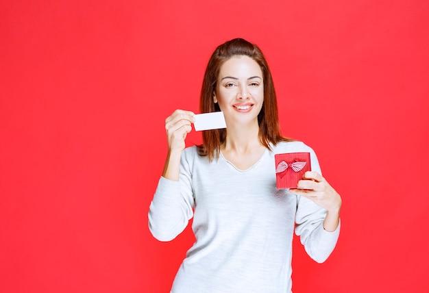 Młoda kobieta w białej koszuli trzymająca małe czerwone pudełko prezentowe i prezentująca swoją wizytówkę
