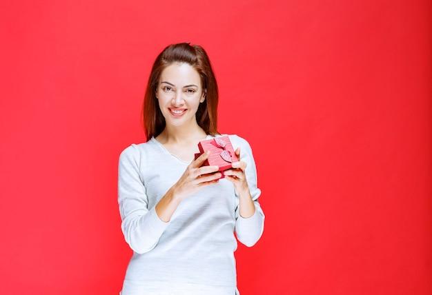 Młoda kobieta w białej koszuli trzymająca małe czerwone pudełko upominkowe