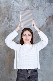 Młoda kobieta w białej koszuli trzymająca nad głową srebrne pudełko upominkowe