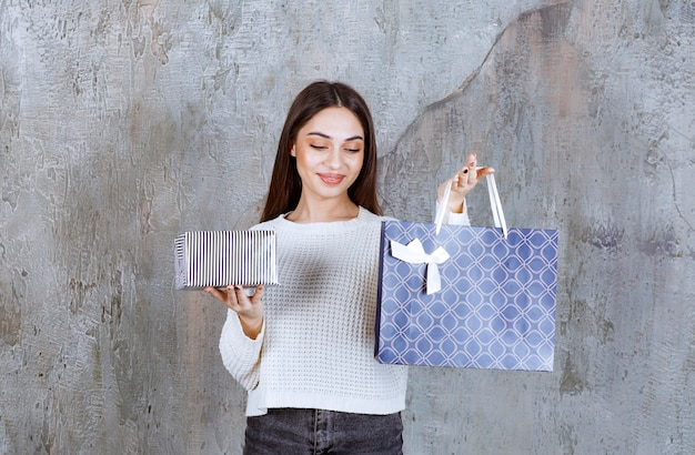Młoda kobieta w białej koszuli trzymająca srebrne pudełko i niebieską torbę na zakupy