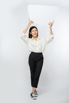 Młoda kobieta w białej koszuli trzymająca symbol skrzynki myśli