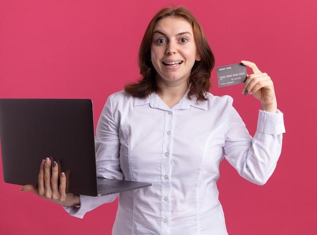 Młoda kobieta w białej koszuli z laptopem pokazując kartę kredytową patrząc na przód uśmiechnięty wesoło stojąc na różowej ścianie