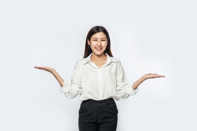 Młoda kobieta w białej koszuli z rozłożonymi rękami