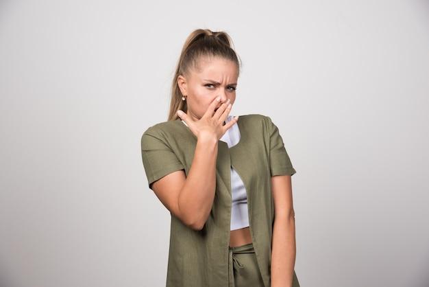 Młoda kobieta w białej koszuli zły na szarej ścianie.