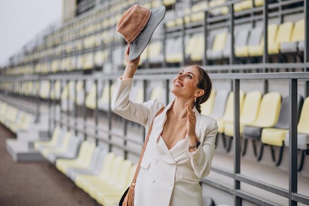 Młoda kobieta w białej kurtce trzymając kapelusz