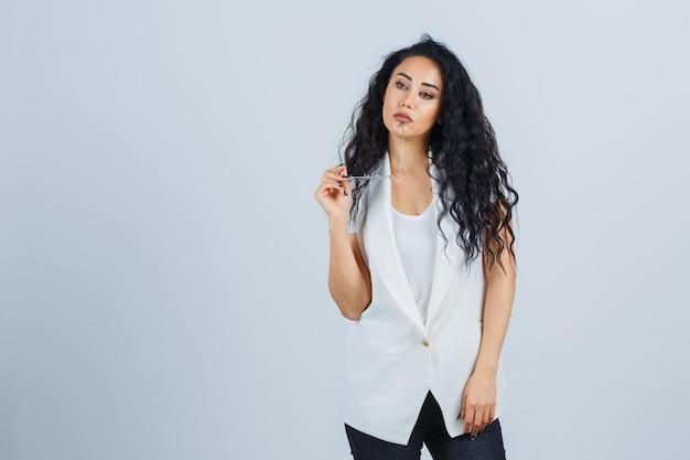 Młoda kobieta w białej kurtce z okularami