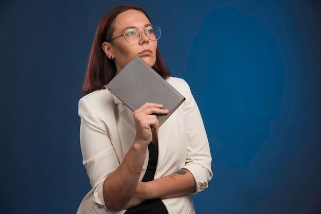 Młoda kobieta w białej marynarce trzyma książkę i myśli.