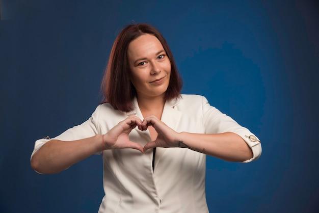 Młoda kobieta w białej marynarce wysyłania miłości.